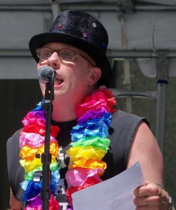 Eli speaks at Disabilty Pride rally, wearing a black tophat with rhine stones and a rainbow boa